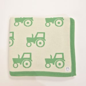 Cream blanket with green tractor pattern and edging